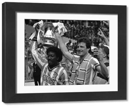 Jubilant Coventry City goal scorers Dave Bennett (left) and Keith Houchen hold the coveted FA Cup aloft after beating Tottenham Hotspur in the final at Wembley
