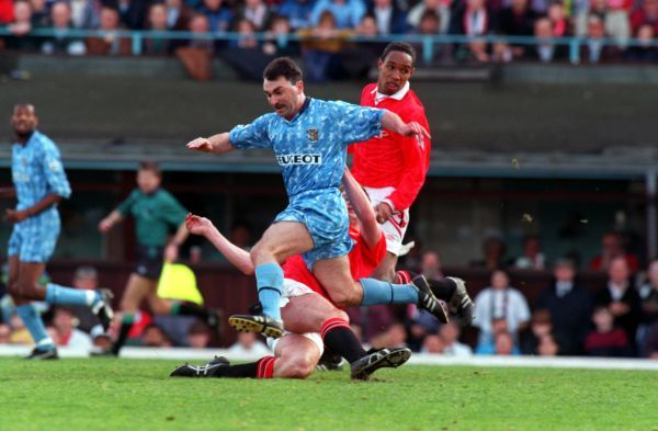Coventry City's Mickey Gynn is tackled by Manchester United's Gary Pallister (on floor) as United's Paul Ince (r) looks
