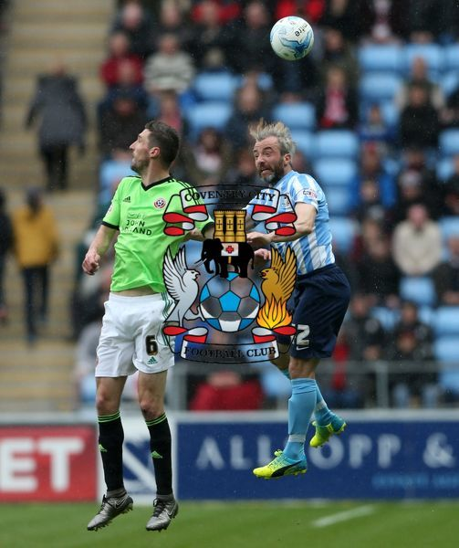 Coventry City's Stephen Hunt and Sheffield United's Chris Basham (left) battle for the ball in the air